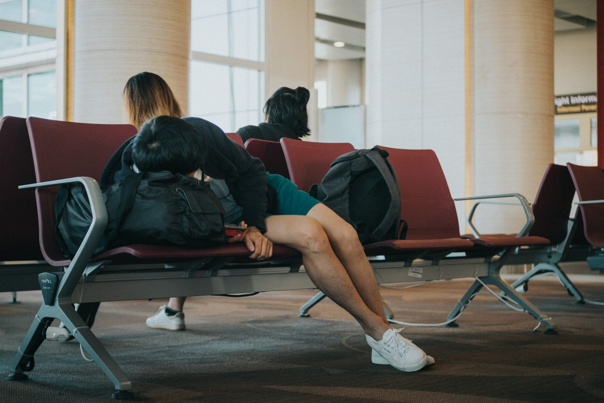 7 Ways Secrets to Beating Jet Lag cover woman sleeping on the airport chair