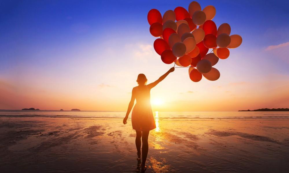 Girl walking on the beach with a bunch of red balloons