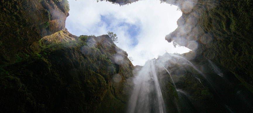 awhum waterfall in the cave with a wonderful sky view