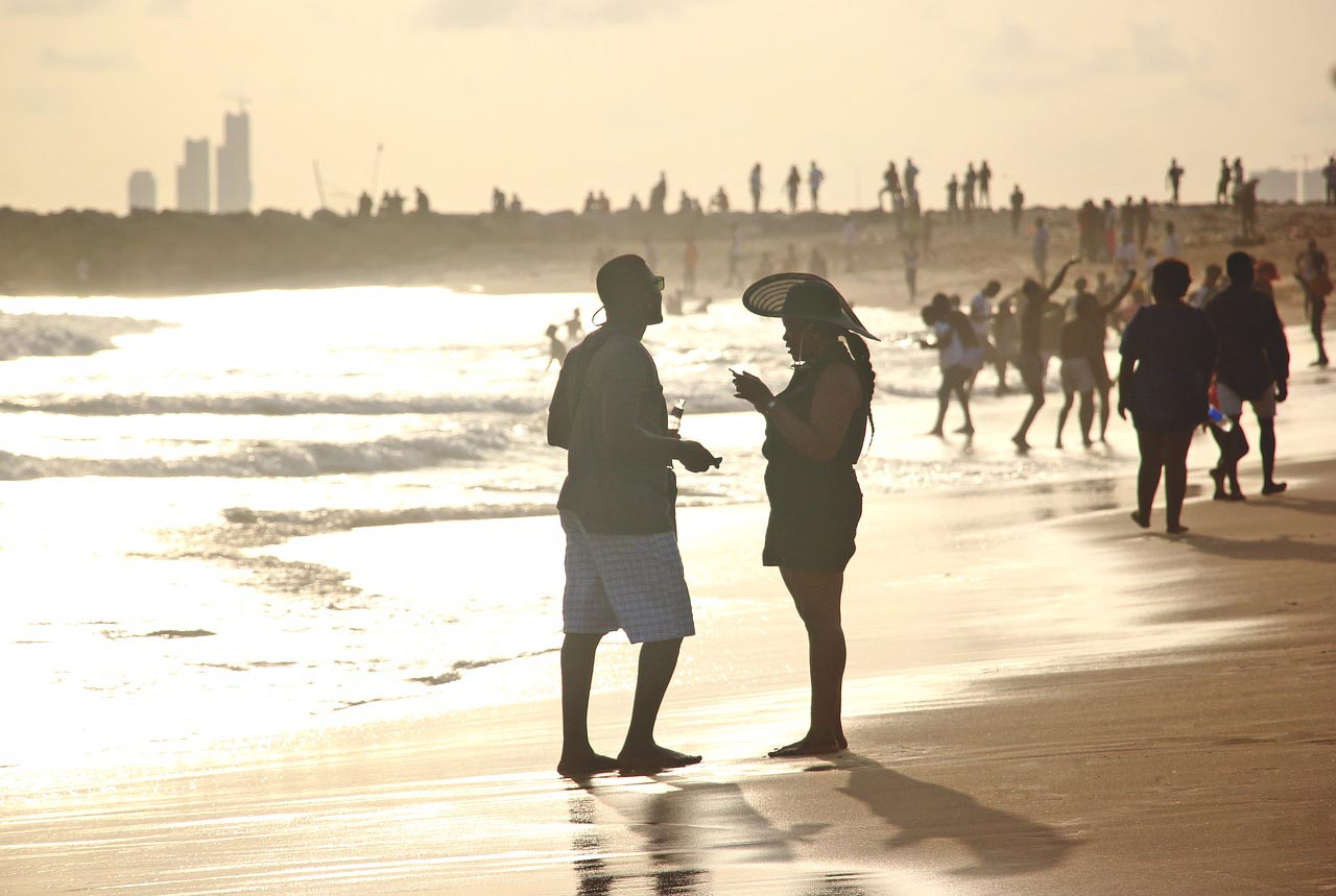 a man and a woman is talking on the beach of the most beautiful states in Nigeria while far away some people are enjoying and walking