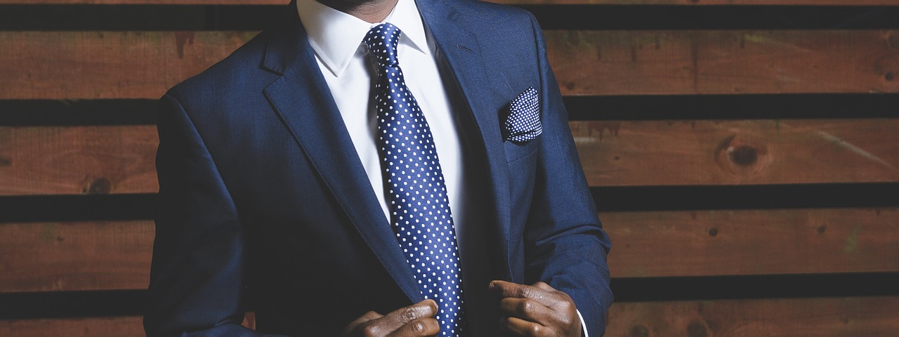 A young african man in dark blue suits doing his button
