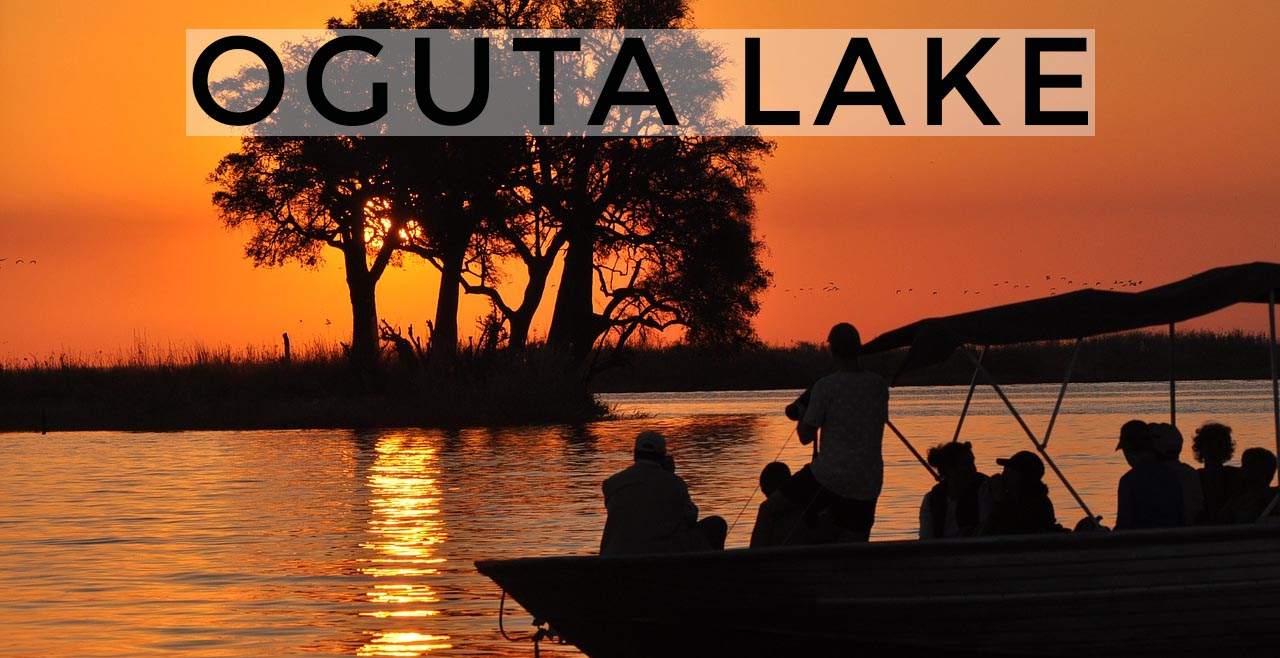 Silhouette of tourist in Oguta lake on a boat taking picture of the magnifique sunset