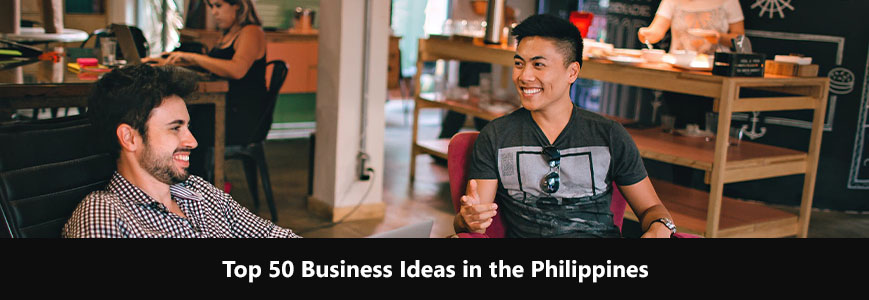 Two men are sitting at the same table in a café. They are laughing and talking about business ideas in the Philippines.