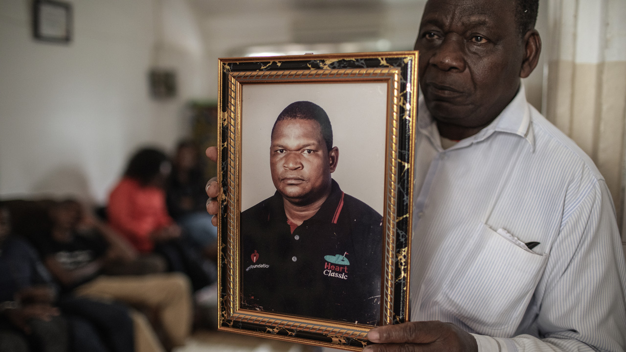 Filipe Mahajane, spokesperson for the Matavele family, holds a portrait of murdered Anastacio Matavele in Mozambique [File: Gianluigi Guercia/AFP]