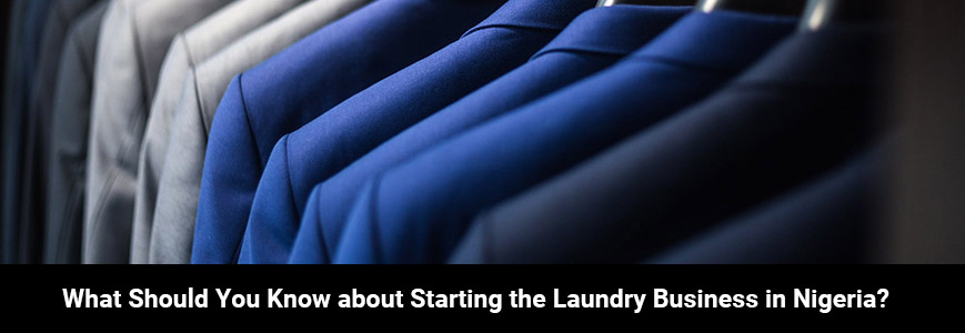Close-up of a dressing room with various shades of blue and gray classic suits in a business laundry in Nigeria
