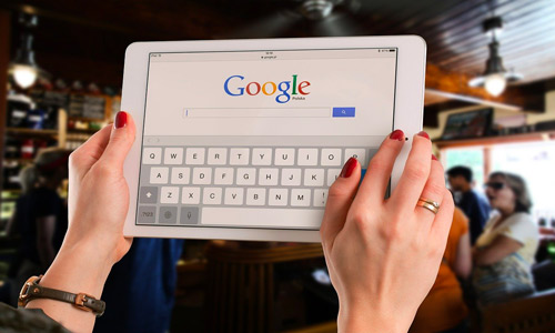Girls hands are holding the tablet to search something on google