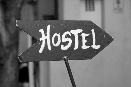 "Black and white photo with a plate writing ""hostel"". Hostel is a big opportunity to make money with land"