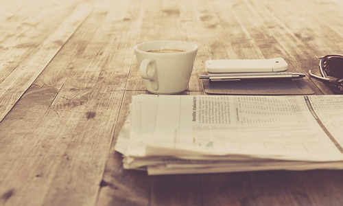 There are newspaper with a cup of coffee, smartphone and a pen. Newspaper is local media, that you can use to boost your business