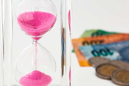 A hourglass with money in the background to save money and time