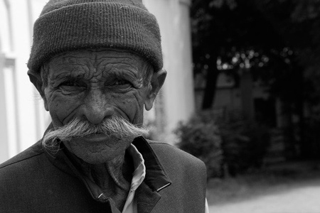 It is black and white photo with a senior, who has a big mustache and he is smiling