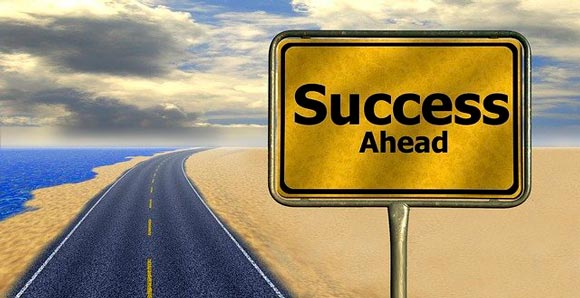 """A road sign with """"success ahead"""" on the road nearby the sea"""