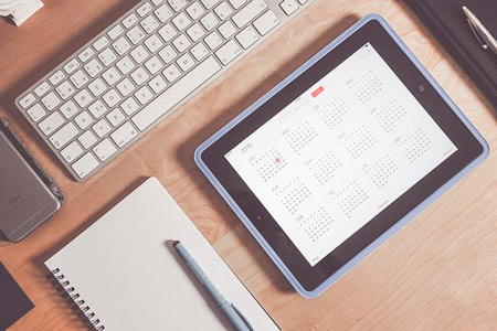 A social media calendar on a tablet with a notebook for your successful business