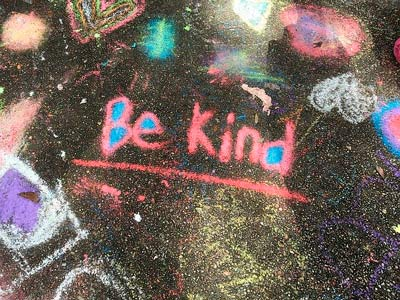 """Be kind"" is written on the asphalt"